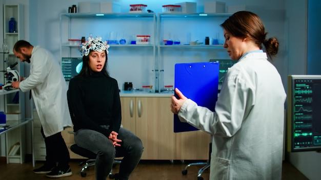Médecin professionnel en médecine neurologique testant la vue d'un patient avec un casque eeg