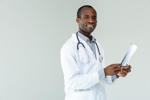 Médecin professionnel positif tenant une radiographie de la poitrine contre le mur blanc