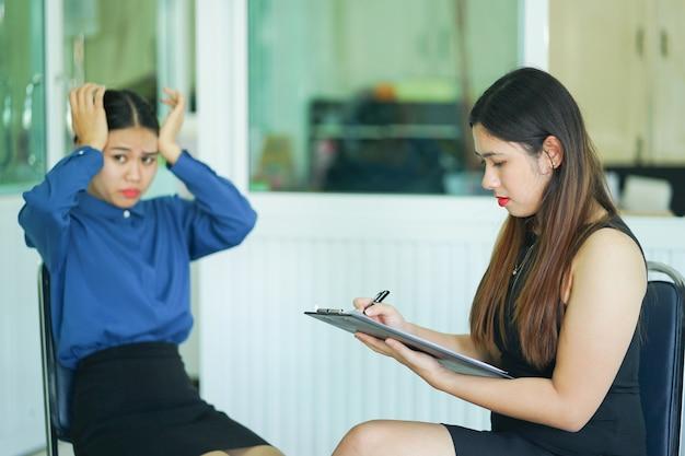 Médecin professionnel de psychologue écrivant l'information du patient au bureau