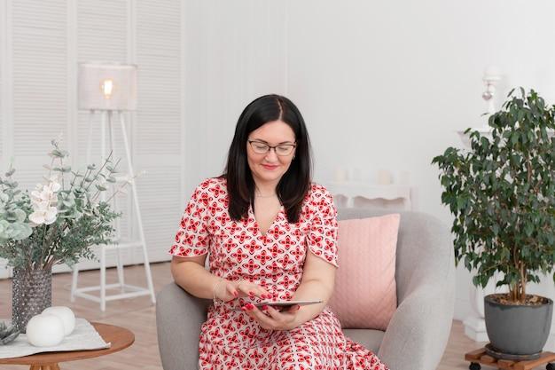 Un médecin psychologue professionnel avec des lunettes est assis dans un bureau lumineux avec une tablette dans ses mains