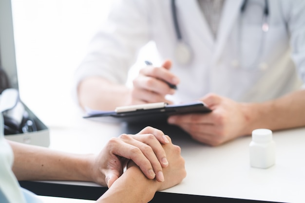 Le médecin qui écoute le patient explique son symptôme et ses notes au dossier médical.