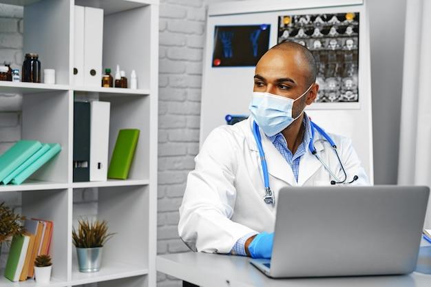 Médecin de race mixte assis à sa table de travail à l'hôpital