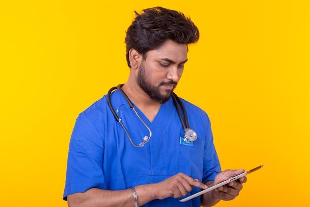 Médecin de race mixte mignon dans une robe bleue avec un stéthoscope en regardant une tablette basée sur un mur jaune. consultation en ligne de concept. copyspace
