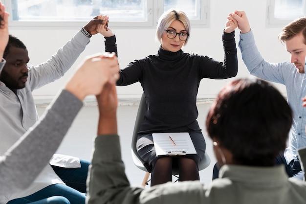 Médecin de réadaptation, levant la main des patients