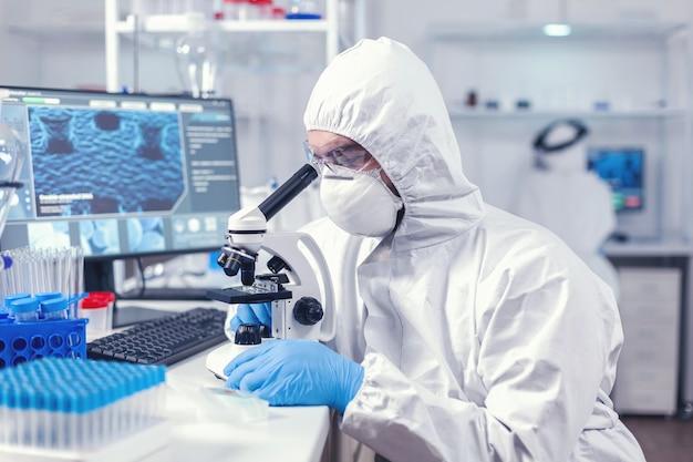 Médecin recherchant et évaluant le virus à l'aide d'un microscope en laboratoire portant un epi. scientifique en tenue de protection assis sur le lieu de travail utilisant la technologie médicale moderne pendant l'épidémie mondiale.
