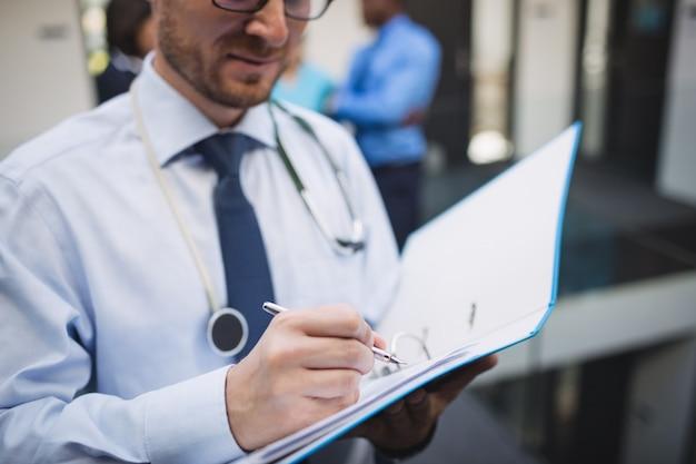 Médecin rédigeant un rapport médical