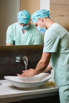 Le médecin regarde la propreté de ses mains après s'être lavé sous un jet d'eau