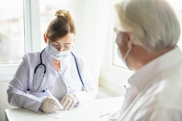 Le médecin remplit la carte de vaccination contre le coronavirus pour un patient âgé pendant la pandémie de covid-19. le concept de vaincre covid-19