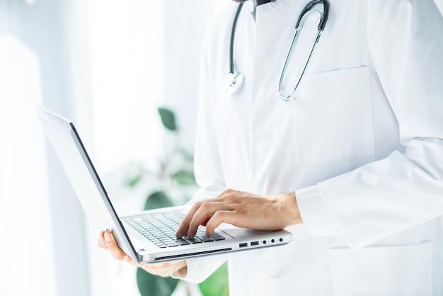 Médecin responsable de la navigation sur ordinateur portable au bureau