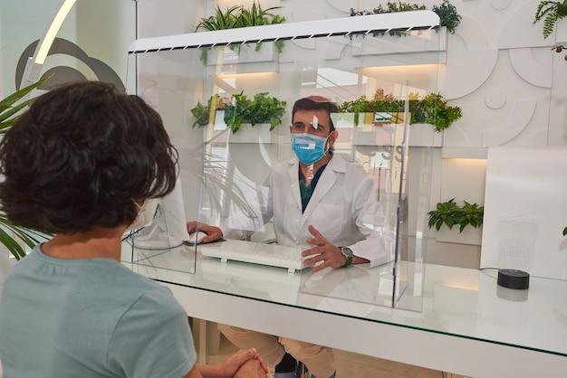 Le médecin s'occupe de son patient, il porte le masque et il y a un écran protecteur. mesures de sécurité contre le covid-19.