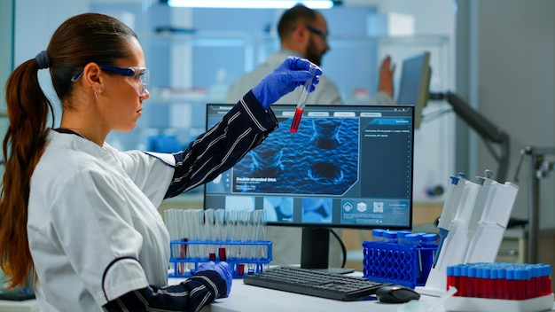 Médecin scientifique regardant un échantillon de sang et tapant sur un ordinateur pendant qu'un collègue ouvre la porte à l'aide d'un ordinateur numérique avec balayage tactile. femme examinant l'évolution du virus à l'aide d'outils de haute technologie et de chimie