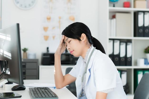 Le médecin se repose dans la salle d'examen elle ressent un mal de tête et du stress.