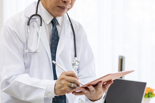 Médecin senior à l'aide d'une tablette