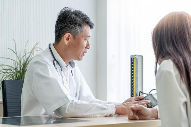 Médecin senior asiatique et patient discutent