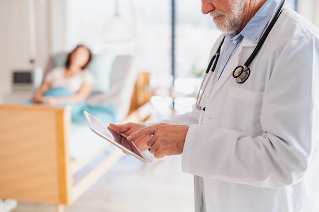 Médecin senior méconnaissable debout dans la chambre d'hôpital, utilisant une tablette.