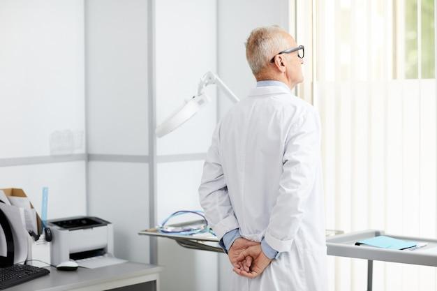 Médecin senior pensif par fenêtre