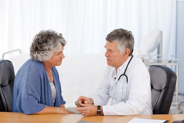 Un médecin senior avec son patient dans son bureau