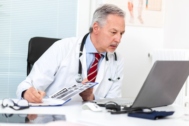 Médecin senior travaillant sur son ordinateur portable dans son studio