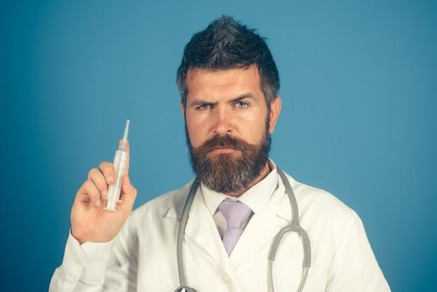 Médecin avec seringue sur fond bleu. médecin de sexe masculin préparant la seringue. traitement à l'hôpital, antibiotiques. concept de santé.