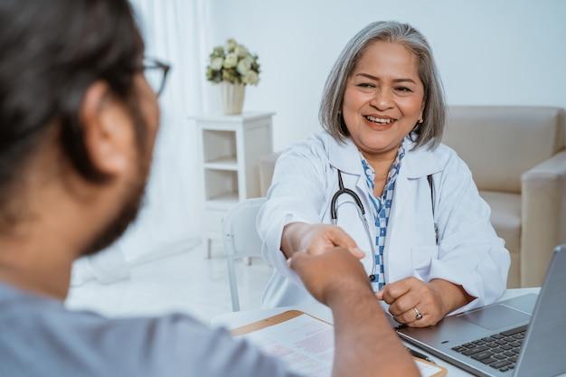 Médecin serre la main du patient