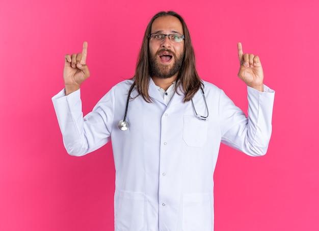Médecin de sexe masculin adulte impressionné portant une robe médicale et un stéthoscope avec des lunettes pointant vers le haut