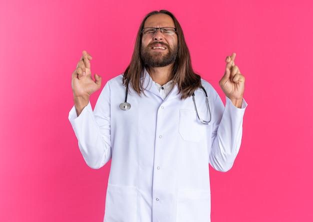 Médecin de sexe masculin adulte plein d'espoir portant une robe médicale et un stéthoscope avec des lunettes faisant un geste de bonne chance avec les yeux fermés isolés sur un mur rose