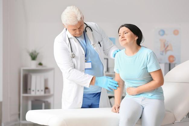 Médecin de sexe masculin d'âge mûr travaillant avec le patient en clinique