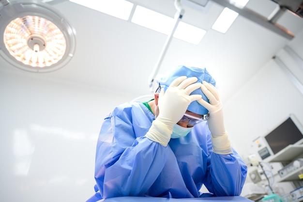 Médecin de sexe masculin assis triste et stressé j'ai été déçu par l'opération dans la salle d'opération de l'hôpital.