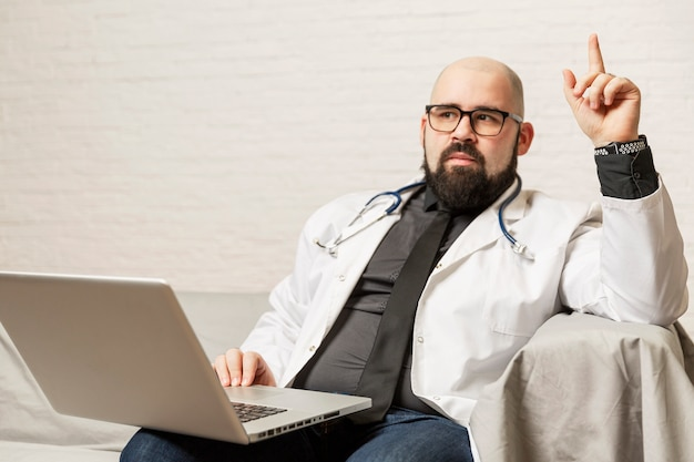 Un médecin de sexe masculin en blouse blanche est assis sur un canapé avec un ordinateur portable. blog et coaching.