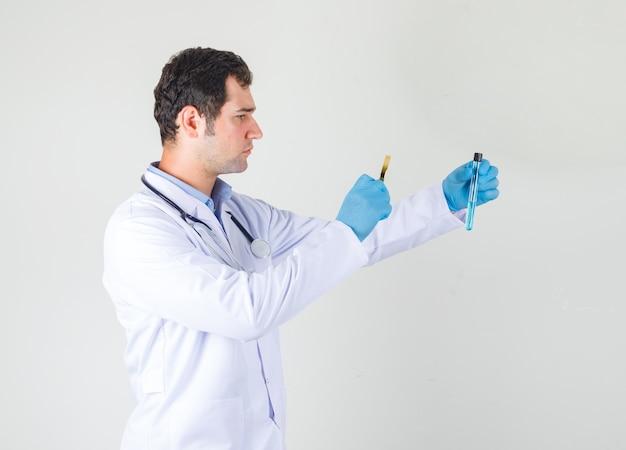 Médecin de sexe masculin en blouse blanche, gants tenant la loupe sur tube à essai et à la recherche de sérieux.