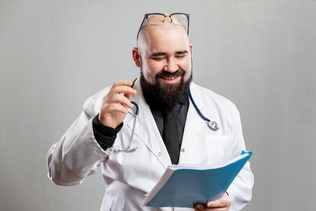Un médecin de sexe masculin en blouse blanche se penche sur les antécédents médicaux et rit