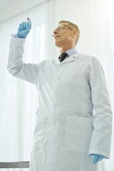 Médecin de sexe masculin en blouse blanche tenant une bouteille de vaccin