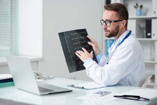 Médecin de sexe masculin confiant en blouse blanche et écouteurs assis devant un ordinateur portable et pointant sur l'image radiographique du patient lors de la consultation en ligne