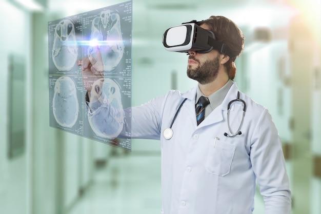 Médecin de sexe masculin dans un hôpital, à l'aide de lunettes de réalité virtuelle, regardant un écran virtuel