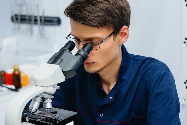 Un médecin de sexe masculin dans le laboratoire étudie les virus et les bactéries au microscope. recherche de virus et de bactéries dangereux.