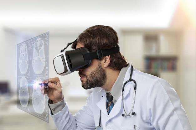 Médecin de sexe masculin dans son bureau, à l'aide de lunettes de réalité virtuelle, regardant un écran virtuel
