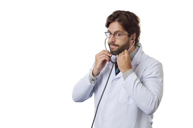Médecin de sexe masculin dans son bureau à l'aide d'un stéthoscope.