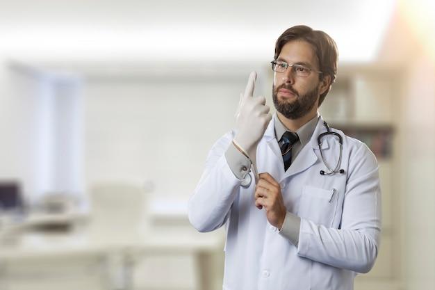 Médecin de sexe masculin dans son bureau, mettre des gants en latex