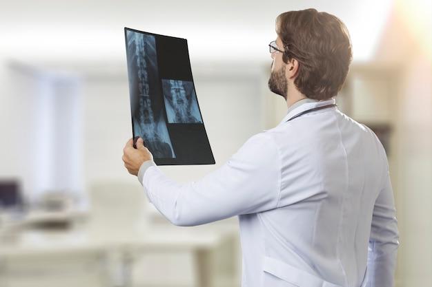 Médecin de sexe masculin dans son bureau à la recherche d'une radiographie
