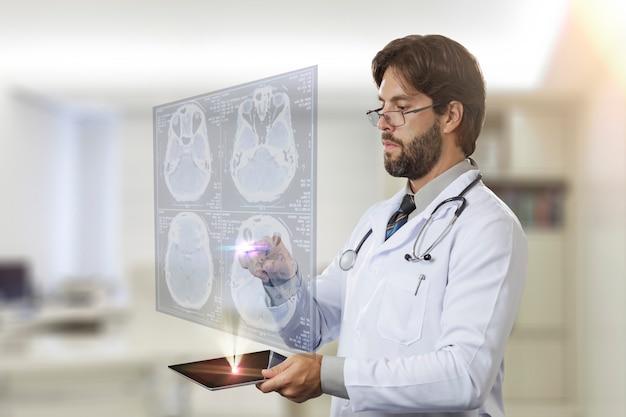 Médecin de sexe masculin dans son bureau, regardant un écran virtuel sortant d'une tablette