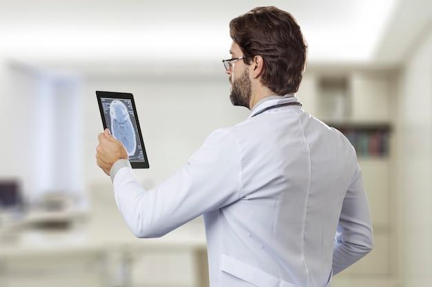 Médecin de sexe masculin dans son bureau, regardant une tablette