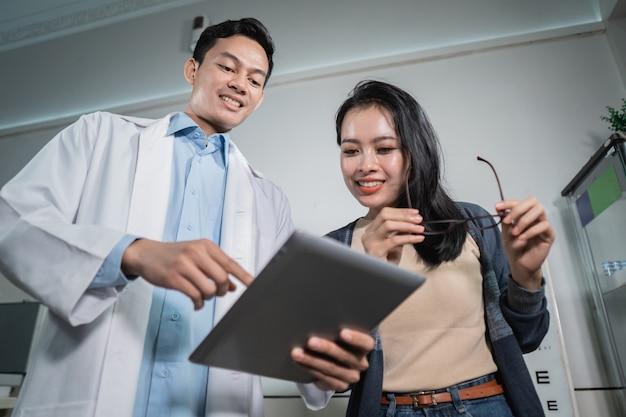 Un médecin de sexe masculin donne les résultats d'une analyse à une patiente qui a subi un examen de la vue dans une clinique ophtalmologique