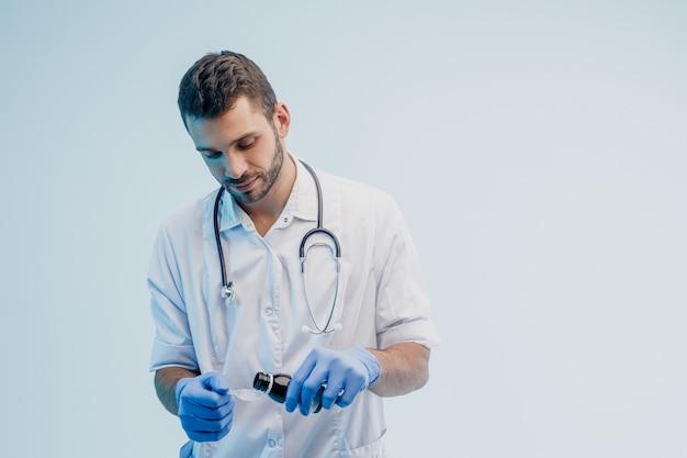 Médecin de sexe masculin européen concentré versant du sirop de la bouteille à la cuillère. jeune homme barbu avec stéthoscope portant une blouse blanche et des gants en latex. fond gris avec lumière turquoise. tournage en studio. espace de copie