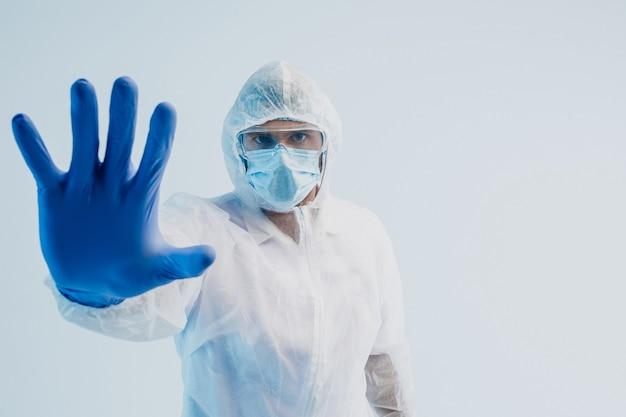 Médecin de sexe masculin européen montrant un geste d'arrêt. homme portant une blouse blanche, des lunettes, un masque de protection et un gant en latex. concept de lutte contre le coronavirus. fond gris avec lumière turquoise. espace de copie