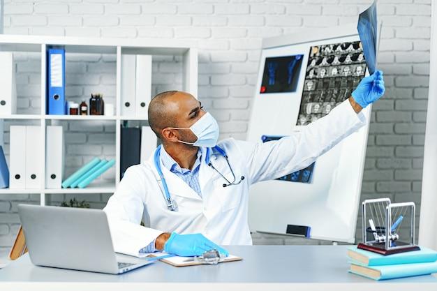 Médecin de sexe masculin examine une radiographie des poumons à l'hôpital