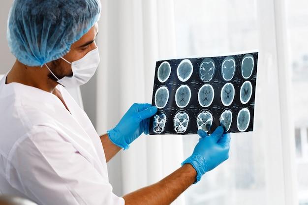 Médecin de sexe masculin examine le scanner cérébral irm d'un patient