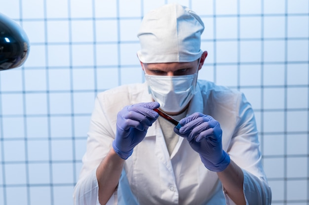 Médecin de sexe masculin avec des fichiers sur un hôpital tenant un presse-papiers et écrivant une ordonnance