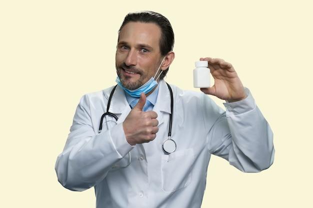 Médecin de sexe masculin avec flacon de médicament montre le pouce vers le haut. bel homme en blouse médicale portant des pilules publicitaires stéthoscope. isolé sur fond jaune.