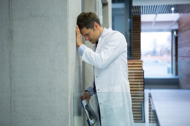 Médecin de sexe masculin inquiet appuyé sur le mur près du couloir