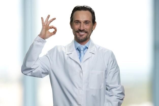 Un médecin de sexe masculin joyeux et joyeux montre un signe ok. faire un cercle avec les doigts. geste d'approbation.